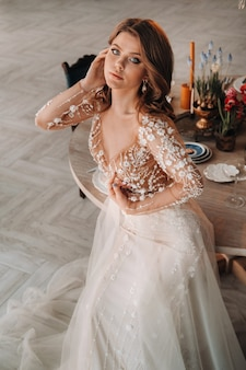 Роскошная невеста в свадебном платье утром в своем интерьере.