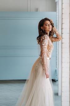 彼女のインテリアで朝のウェディングドレスの豪華な花嫁。