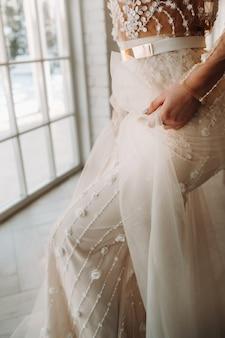 彼女のインテリアで朝のウェディングドレスの豪華な花嫁