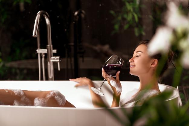 豪華な女の子がワインを片手に泡風呂でリラックスしています。スパとリラクゼーション