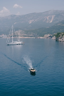 豪華な木製スポーツモーターボートは、沖合に停泊している大きな白いボートからvipを届けます
