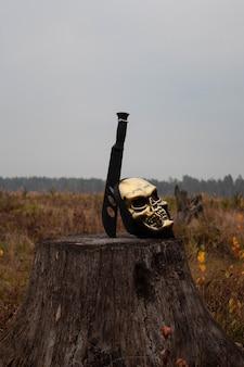 Мачете застряло в пне рядом с маской скелета страшного хэллоуина.