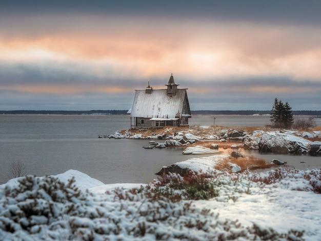 포메라니안 마을의 환상적인 일몰. 러시아 마을 rabocheostrovsk의 해안에 정통 집 눈 덮인 겨울 풍경.