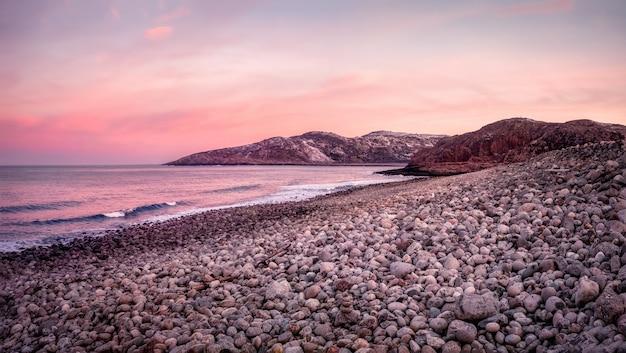 魔法の夕日。海岸の小石。北の海のビーチの表面は、さまざまなサイズの灰色の大きな磨かれた丸い石で覆われています。チェベルカ。