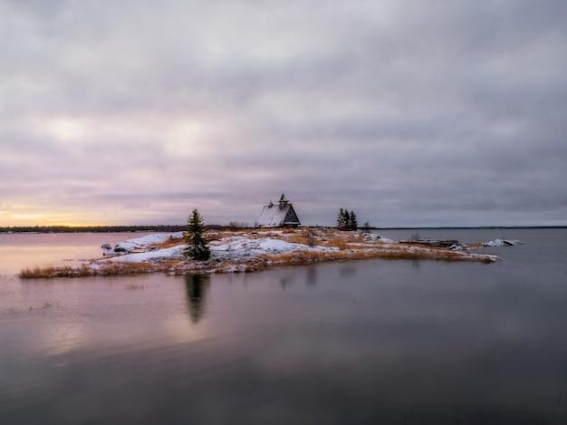 나무로 된 오래된 낚시 롯지가있는 섬의 마법 같은 황혼의 전망.