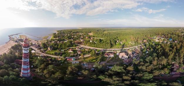 등대, 해안선, 숲속의 집들이 보이는 장엄한 파노라마.