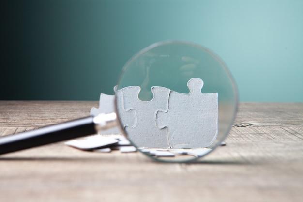 Увеличительное стекло и кусочки пазла на столе