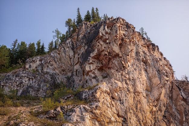 Величественная скала, поросшая лесом, на фоне голубого неба треккинг по красоте природы