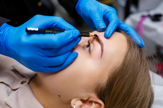 メイクアップアーティストは、眉ペンシルで若い女の子の眉毛にスケッチを適用します。プロのメイクアップと化粧品のスキンケア。