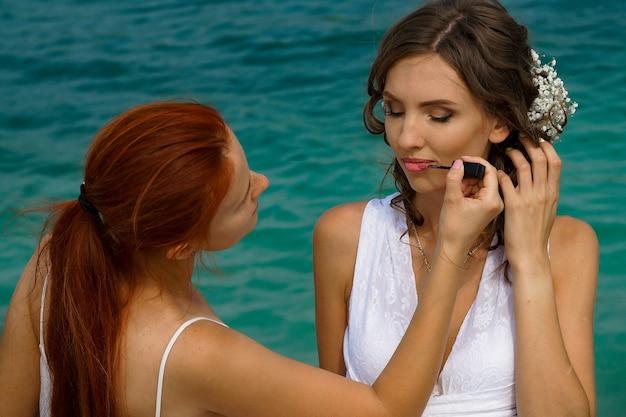 Визажист составляет невесту в белом платье с цветами в волосах на фоне голубого озера и белого песка