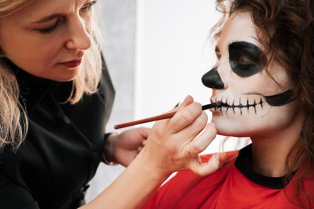 Визажист изображает демона молодой девушке в салоне красоты. концепция празднования хэллоуина.