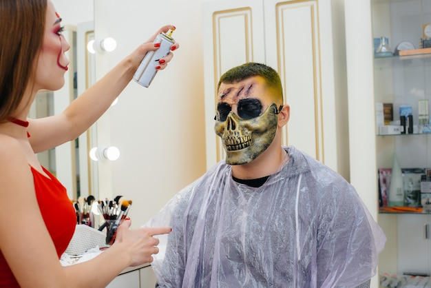 메이크업 전문가 소녀는 스튜디오에서 할로윈 휴가를 위해 남자를 위해 축제 분위기의 소름 끼치는 화장을 합니다. 해피 할로윈 개념입니다.