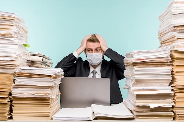 Бухгалтер-мужчина или руководитель компании работает в офисе в условиях пандемии из-за накопленной бумажной работы. - я