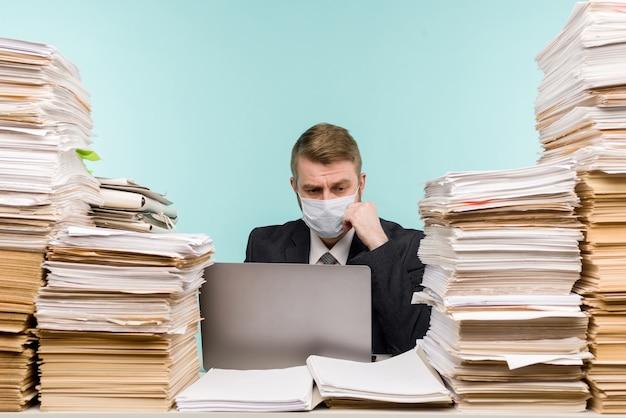 Бухгалтер-мужчина или руководитель компании работает в офисе в условиях пандемии из-за накопленной бумажной работы.