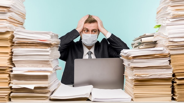 Бухгалтер-мужчина или руководитель компании работает в офисе в условиях пандемии ввиду накопленной бумажной работы