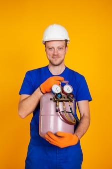 Мужчина-ремонтник кондиционера держит в руках фреоновый цилиндр для кондиционера.