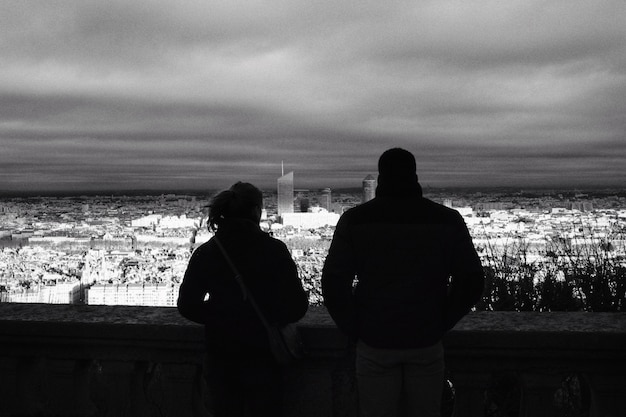 Мужчина и женщина, наслаждаясь видом на город вечером