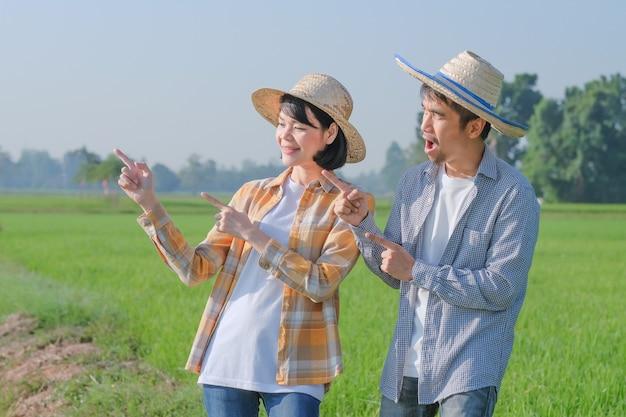 한 남성과 여성의 아시아 농부가 들판을 옆으로 가리키며 기뻐하며 포즈를 취하고 있습니다.