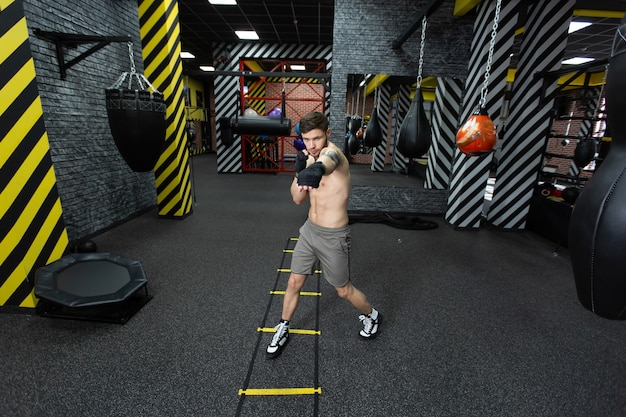 Спортсмен-мужчина тренируется в спортзале.