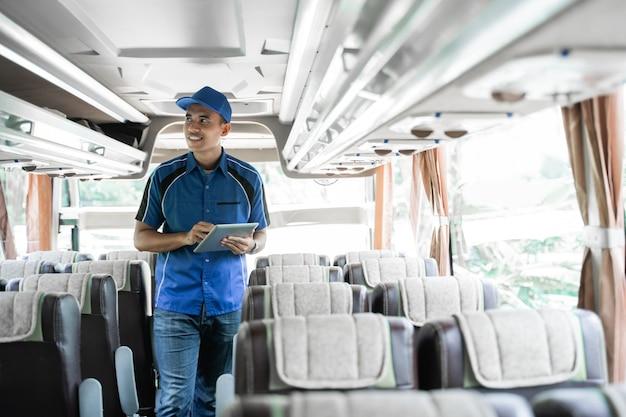 남성 버스 승무원이 디지털 태블릿을 사용하여 버스 내부 선반을 확인합니다.