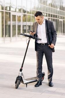 Мужчина-бизнесмен подходит к электросамокату и использует приложение для мобильного телефона экологический транспорт