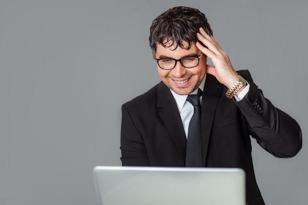 Мужской бизнесмен в черном костюме и очки с ноутбуком.