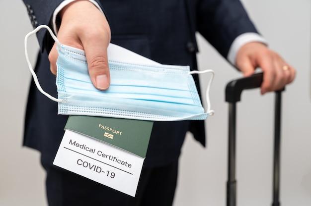 Covid-19の健康証明書とパスポートを持っている男性実業家。 covid-19後のビジネスコンセプト。
