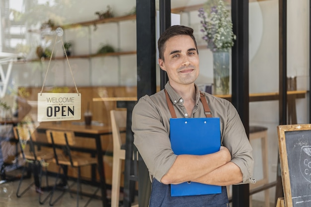 店の前に立っている男性カフェの従業員が客を迎え、店が開いていることを示すためにオープンと書かれた看板があり、男性従業員が食べ物や飲み物を提供するために店を開きます。