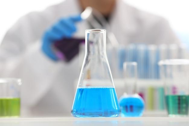 Мужчина-химик держит в руке пробирку из стекла, переливает через край жидкий раствор перманганата калия, проводит анализ реакции