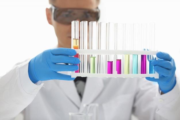 Мужской химик держит пробирку из стекла, в руке переливается жидкий раствор