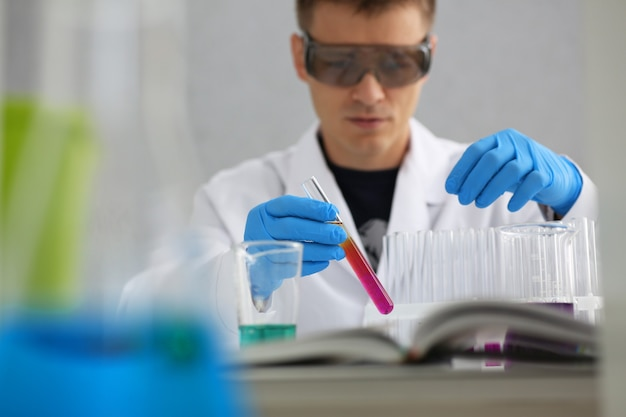Мужчина-химик держит в руке стеклянную пробирку, переливая жидкий раствор