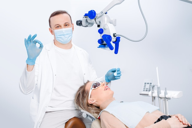 Мужчина-дантист в маске и пациентка в кресле дантиста