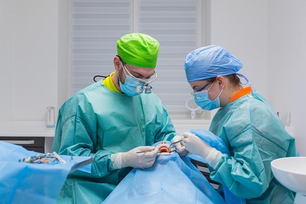 Стоматолог-мужчина в униформе выполняет операцию по имплантации зубов пациенту в стоматологическом кабинете.