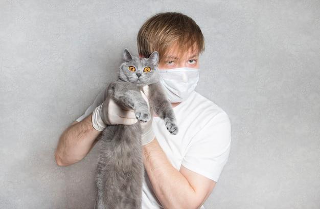 Врач-мужчина ветеринар в маске держит в руках кота pet health
