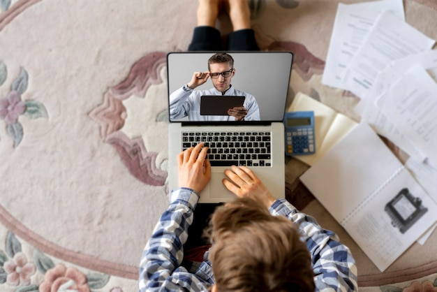 ノートパソコンのウェブカメラで検査をしている男性医師が自宅の患者にオンラインで電話をかける