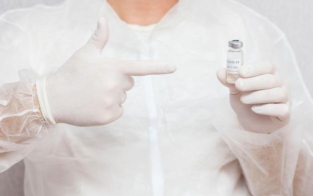 男性医師はcovid-19ワクチンを持っており、指を彼女の方向に向けています。ヘルスケアと医療の概念。