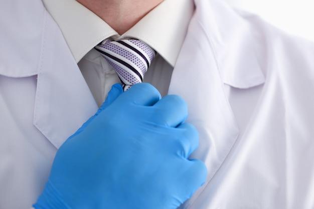ガウンとシャツを着た男性医師がネクタイを調整します