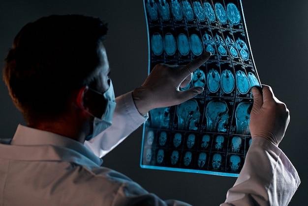 마스크를 쓴 남성 의사가 블랙에 고립 된 환자 뇌 스캔의 x- 레이 또는 mri 스캔을 검사합니다.