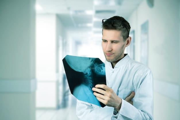 X線人間のスキャンを保持し、それを調べる病院の医療服を着た男性医師 Premium写真