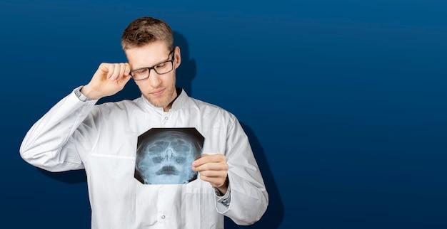 X線人間スキャンを保持し、健康上の問題を検出するためにそれを検査する病院の医療ユニフロムの男性医師