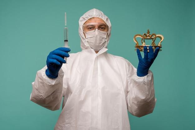 보호 작업복과 마스크를 쓴 남성 의사가 백신과 왕관이 든 주사기를 손에 들고 있습니다. 중국의 coronovirus 보호 개념.