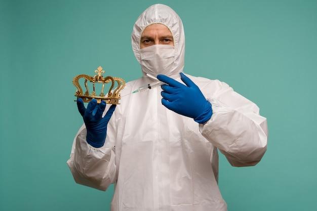 保護オーバーオールとマスクを着用した男性医師がクラウンに注射を行います。中国におけるコロナウイルス保護の概念。