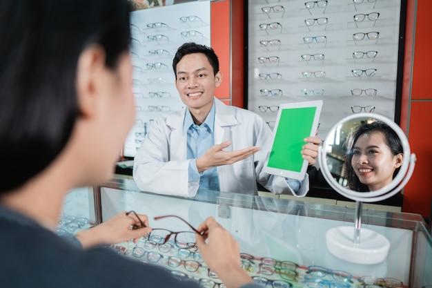 男性医師が眼科クリニックでの目の検査の基本のひとつであるカラーテストボードを見せています