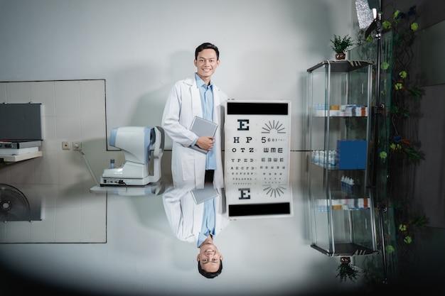 眼科クリニックの診察室にある視力検査キットの横でポーズをとる男性医師