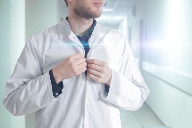 男性医師が病院で医療用ガウンの制服を着て、クリニックの若い専門家