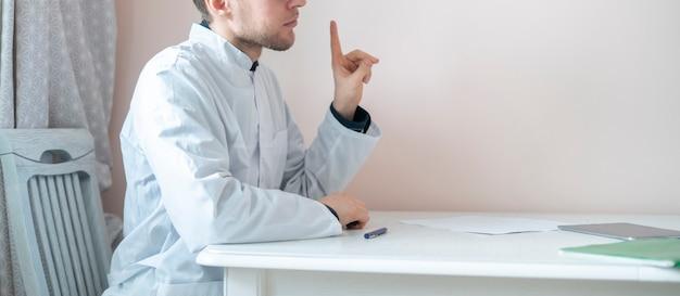 テーブルに座って病院で患者の話を聞く男性医師