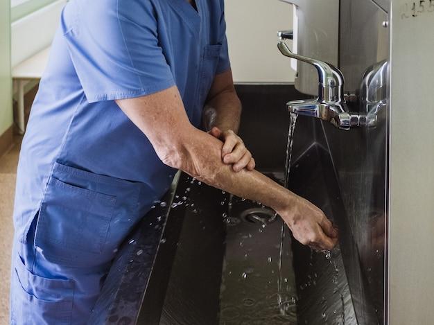 男性医師は、ステンレス製の流しの流水の下で石鹸で手を完全に洗います。必要な消毒対策。