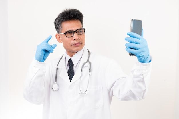 Врач-мужчина разговаривает по телефону с пациентом по видеосвязи, чтобы дать совет.