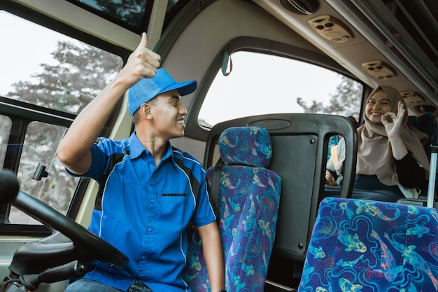 青い制服を着た男性の運転手が、バスに座っている間にバスが出発する合図として乗客に親指を立てた