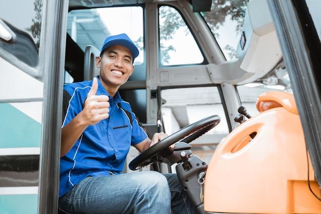 버스에서 바퀴 뒤에 앉아있는 동안 엄지 손가락으로 카메라에 균일 한 미소를 짓는 남성 운전자